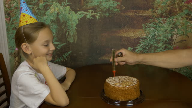 Girl-clapping-by-hands-Sitting-girl-afraid-of-fire-Sparkling-fire-fountains-in-a-cake-Girls-Birthday-Cake-with-lights-Mans-hand-fire-with-lighter-fire-fountain-