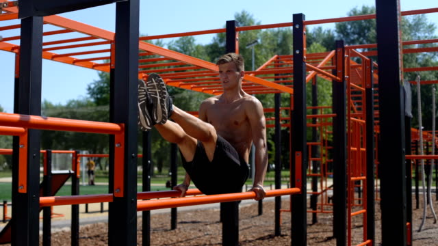 Topless-athlete-performing-abdominal-exercises-on-the-parallel-bars-50-fps