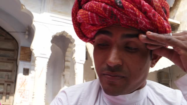 Close-up-of-Rajasthani-couple-tense-worried-sweating-remorse-in-traditional-dress-in-from-of-traditional-architecture-gate