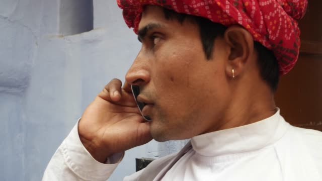 Handsome-dapper-cool-Indian-man-in-Rajasthani-traditional-wear-and-red-turban-busy-on-his-mobile-phone