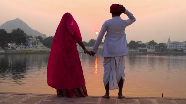 Romantic-Indian-couple-in-traditional-dress-watching-the-sun-go-down-on-Pushkar-lake
