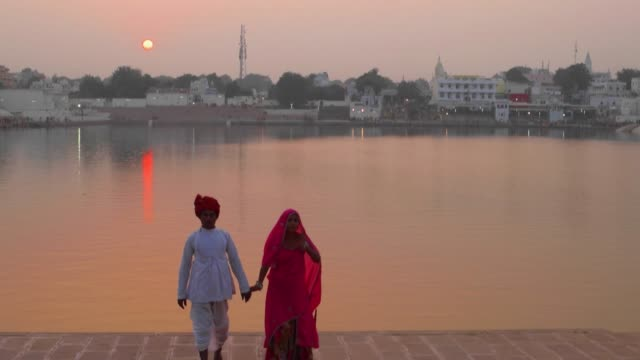 Romantic-Indian-couple-in-traditional-dress-walking-away-from-a-sunset-on-a-lake