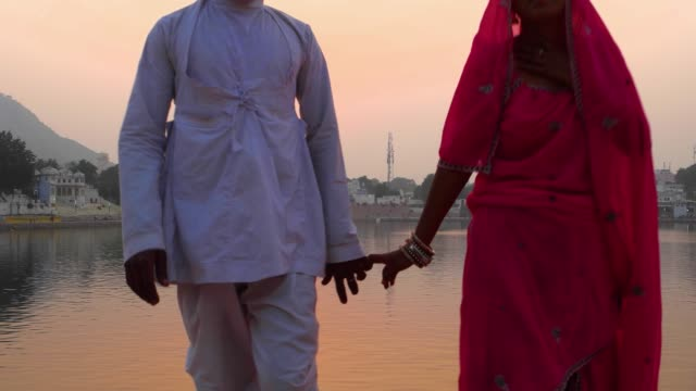 Couple-walk-towards-camera-and-beyond-against-the-setting-sun