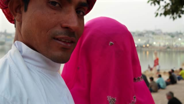 Closeup-handheld-portrait-of-Indian-husband-with-turban-and-shy-wife-in-sari-traditional