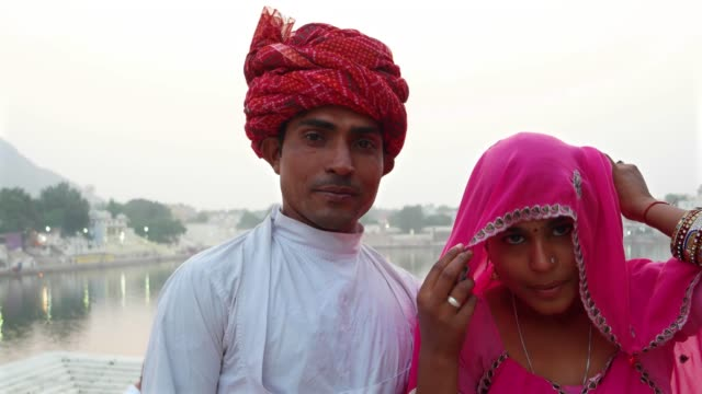 Portrait-of-Indian-husband-with-turban-and-lovely-wife-in-sari-in-front-of-Pushkar-Lake-Rajasthan-India