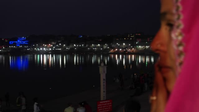 Pan-left-Indian-traditional-romantic-couple-at-Pushkar-Lake-in-night