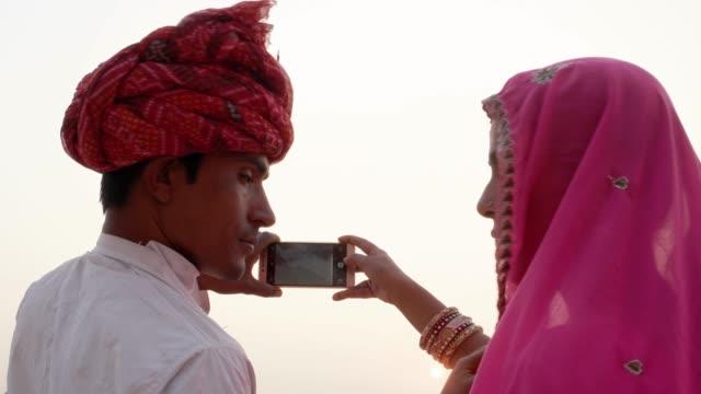 Indian-couple-looking-back-at-the-camera-and-taking-photos-of-sunset-at-holy-Pushkar-lake-Rajasthan