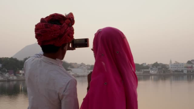 Pan-away-from-Indian-couple-in-traditional-dress-taking-photos-of-sunset-at-holy-Pushkar-lake-Rajasthan