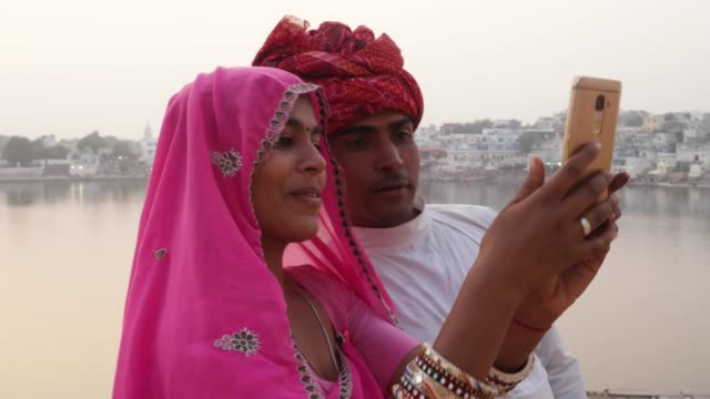 Mano-par-de-Rajasthani-tomar-autorretratos-de-una-cámara-de-teléfono-móvil-en-el-lago-de-Pushkar-India