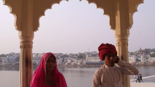 Tilt-down-to-attractive-Indian-couple-in-traditional-dress-with-Pushkar-lake-in-the-background-Rajasthan-India