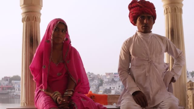 Beautiful-Indian-couple-in-traditional-dress-sitting-with-Pushkar-lake-in-the-background-Rajasthan-India