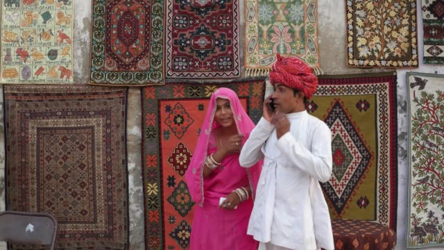 Indian-couple-in-traditional-clothes-enter-the-frame-and-attend-a-phone-call-with-traditional-carpets-hanging-in-the-backdrop