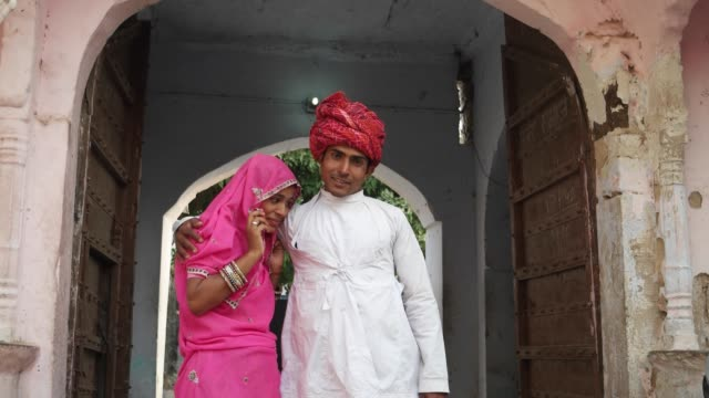 Indian-couple-standing-and-posing-for-camera-in-from-of-their-old-traditional-house-in-Rajasthan-india