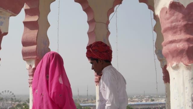Handheld-shot-of-beautiful-Indian-couple-walking-upto-a-view-point-in-Pushkar-Rajasthan-India