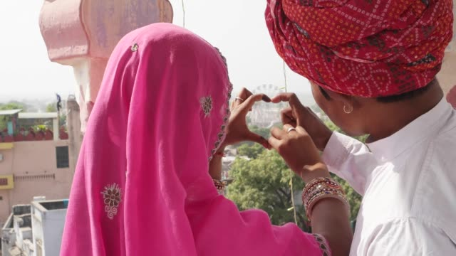 Attractive-Indian-couple-making-a-heart-sign-with-their-hands-overseeing-the-Pushkar-Mela-festival-in-Rajasthan-India
