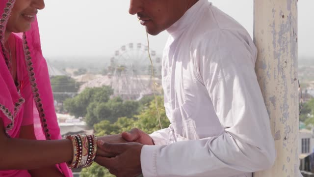 Romantic-couple-dating-at-a-secret-location-with-view-of-a-carnival-in-the-backdrop-in-pink-sari-red-turban-and-white-kurta