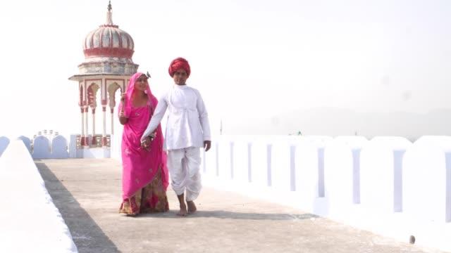 Gran-tiro-de-guapo-masculino-y-hermosa-mujer-caminar-con-confianza-hacia-la-cámara-en-un-tejado-en-Rajasthan-India