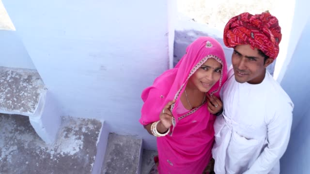 handheld-overhead-shot-of-Beautiful-bride-and-groom-waving-goodbye-from-a-staircase-posing-dolly-in-in-Pushkar-Rajasthan-India