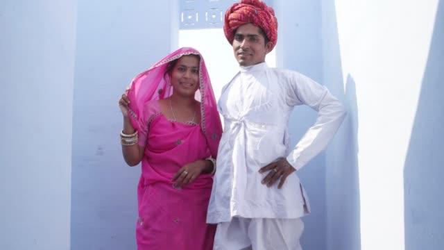 Mujer-en-sari-rosa-camina-hasta-un-hombre-de-turbante-rojo-y-blanco-kurta-y-pose-para-la-cámara-en-Rajasthan-India