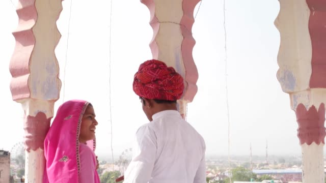 Tilt-down-to-dating-girl-and-boy-under-a-rooftop-canopy-chattri-talking-in-Rajasthan-India-in-pink-sari-and-red-turban-and-white-kurta