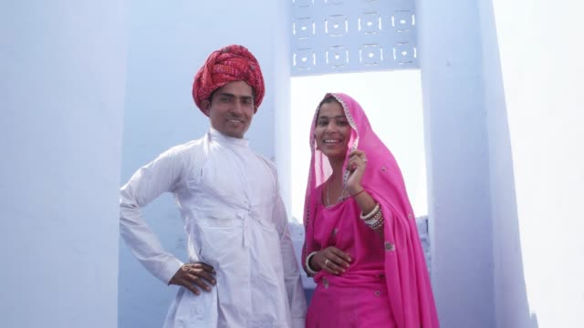 Focus-shift-to-a-gorgeous-traditional-bride-and-groom-in-traditional-wear-against-a-blue-background-in-India
