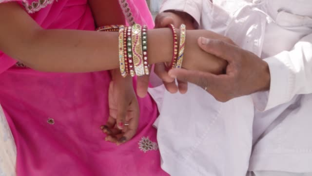 Traditional-Indian-bride-with-pink-sari-multi-coloured-bangles-seated-with-her-husband-with-a-view-of-carnival-in-the-backdrop-in-Rajasthan-during-Pushkar-Mela