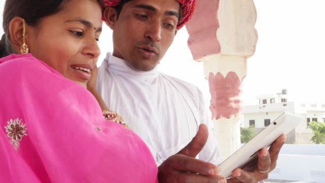 Traditional-Indian-wife-and-husband-working-learning-teaching-on-a-tablet-in-Rajasthan-India