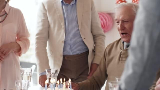Anciano-soplado-de-velas-en-fiesta-de-cena-de-cumpleaños