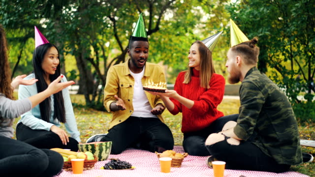 Bearded-African-American-guy-is-having-birthday-party-in-park-blowing-candles-on-cake-and-laughing-enjoying-surprise-his-friends-are-clapping-hands-