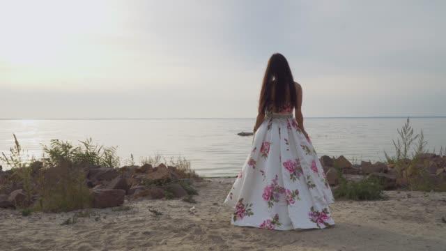 Pretty-girl-in-a-long-beautiful-dress-walks-by-the-river