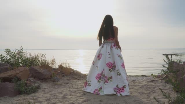 Cute-girl-in-a-long-beautiful-dress-walks-by-the-river