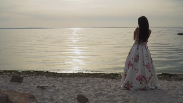 Nice-young-girl-in-a-long-beautiful-dress-walks-by-the-river