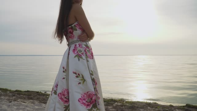 Charming-girl-in-a-long-dress-standing-by-the-river