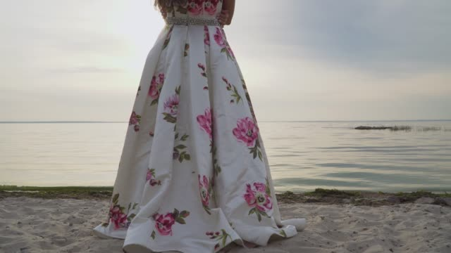 Charming-brunette-in-a-long-evening-dress-standing-by-the-river