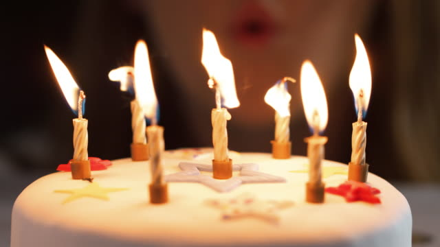 Close-up-of-a-woman-blowing-out-seven-lit-candles-on-a-white-decorated-birthday-cake-a-party-blower-beside-it-bokeh-lights-in-the-background-detail