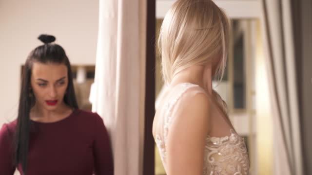 Un-carro-de-una-parte-central-de-la-velo-bordado-vestido-de-lujo-con-flecos-usado-por-una-rubia-bastante-joven-Ella-está-dando-la-vuelta-frente-al-espejo-y-se-mira-el-diseñador-Hablan-