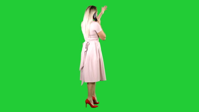 Standing-young-beautiful-girl-making-a-call-on-a-Green-Screen-Chroma-Key