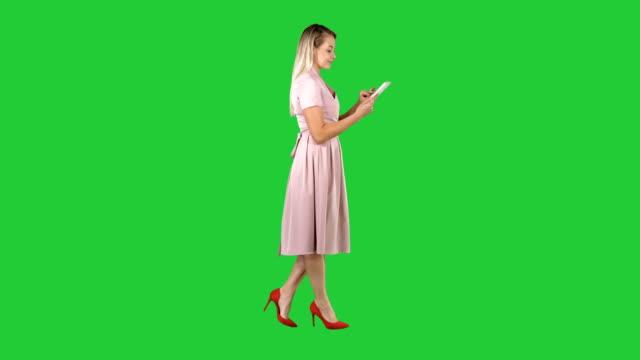Rubia-en-rosa-Vestido-de-a-pie-y-uso-de-tableta-a-una-pantalla-verde-Chroma-Key