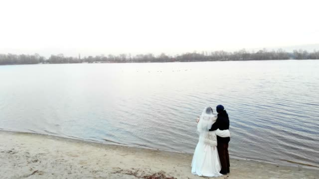 KIEV-KYIV-UKRAINE---NOVEMBER-18-2018-:-Aerial-view-of-the-Dnieper-River-embankment-in-Kiev-winter-wedding-newlywed-couple-in-wedding-clothes-enjoy-the-view-sunset