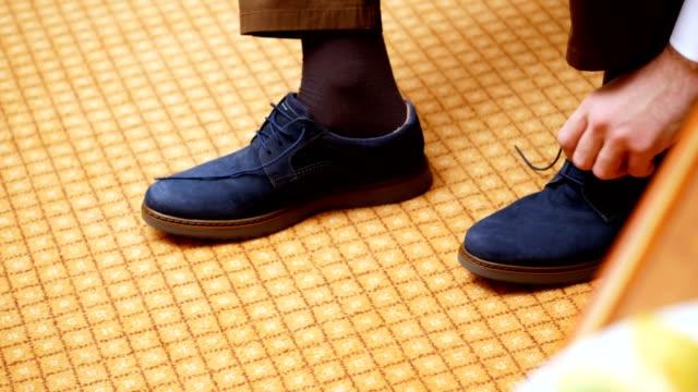 primer-plano-las-manos-de-los-hombres-atan-cordones-de-los-zapatos-hombre-se-pone-sus-zapatos-de-gamuza-azul-elegante-en-el-fondo-de-la-alfombra-Preparación-para-la-boda-del-novio