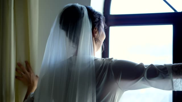 portrait-of-a-bride-beautiful-girl-in-veil-and-white-peignoir-robe-pushes-the-curtains-looks-out-the-window