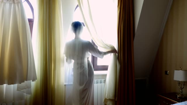 a-bride-beautiful-girl-in-veil-and-white-peignoir-robe-looks-out-the-window-Morning-of-the-bride