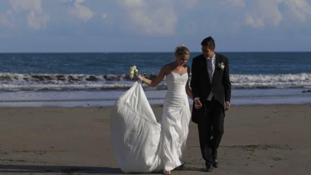 Happy-newlywed-couple-walking-on-the-beach
