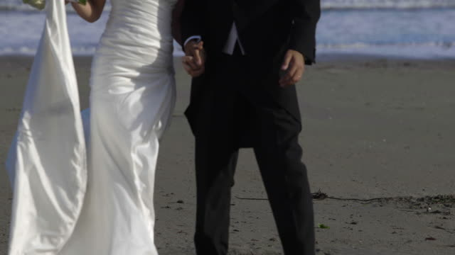 Smiling-newlywed-couple-walking-on-the-beach