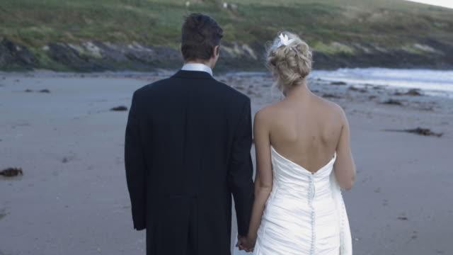Smiling-newlyweds-walking-on-the-beach