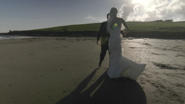 Smiling-newlyweds-dancing-on-the-beach