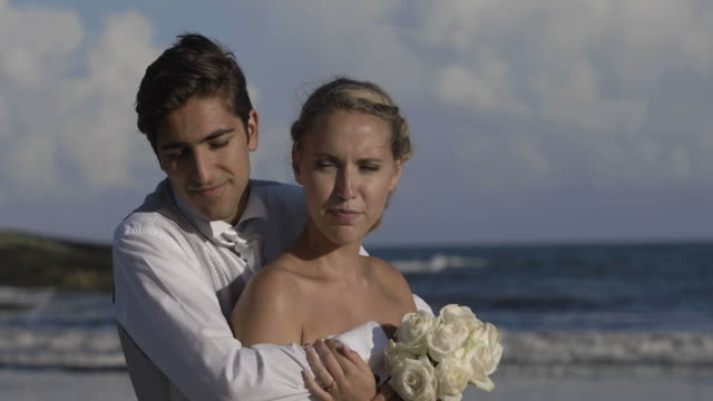 Smiling-newlyweds-hugging-on-the-beach