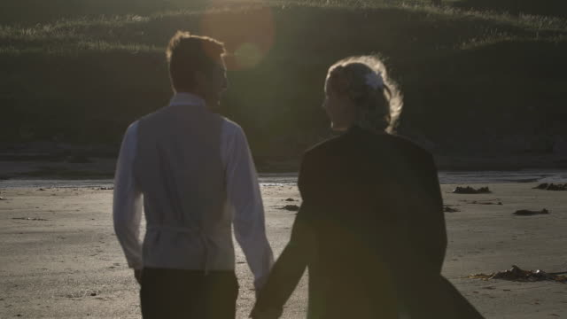 Smiling-newlyweds-walking-together-on-the-beach