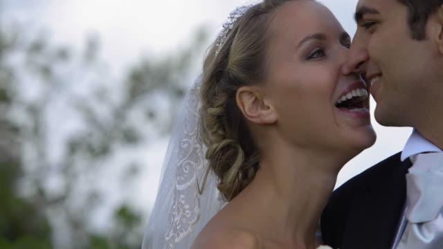 Laughing-newlyweds-kissing-outside