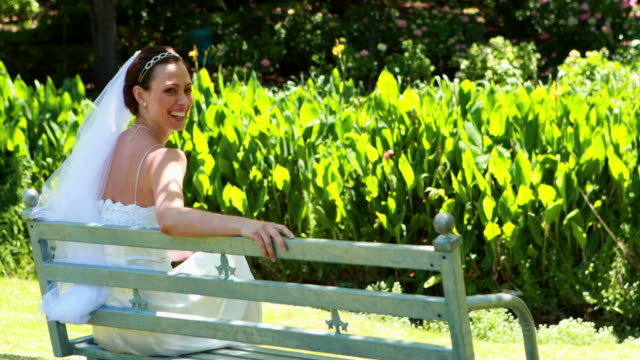 Beautiful-bride-smiling-at-camera-sitting-on-bench